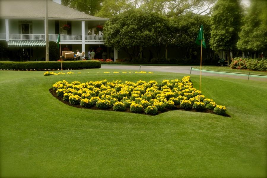 Iconic roundabout in front of the Augusta National clubhouse. Photo via Wikimedia Commons under the Creative Commons license [http://upload.wikime dia.org/wikipedia/co mmons/b/b6/August aNationalMastersLo goFlowers.jpg]