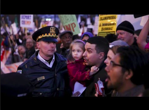 Protesters at a Trump rally with a Police Officer. Photo via Youtube under the Creative Commons license. ( https://www.youtube.com/watch?v=3CUaqfPiqq4 )