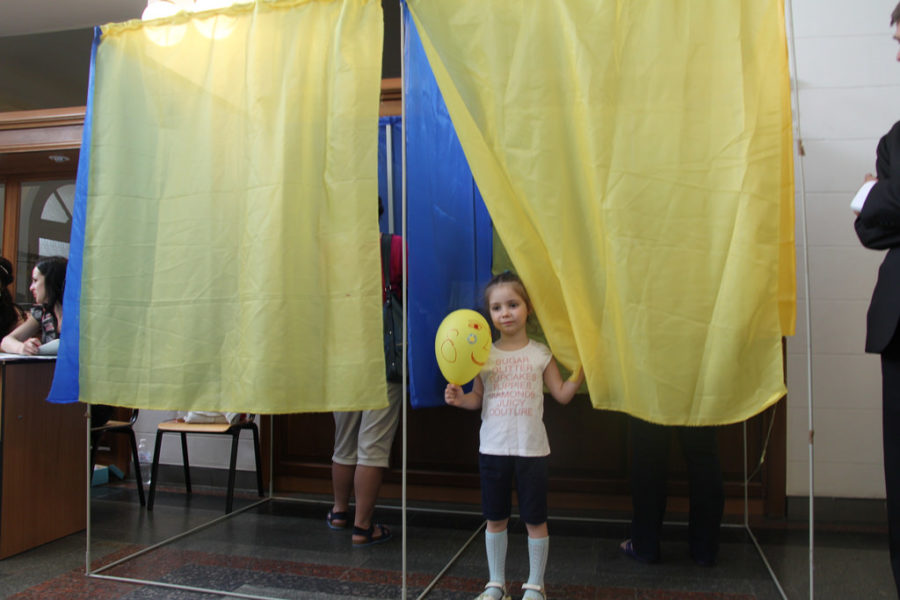 A young child standing at a voting booth. Label for reuse by the Wikimedia Commons.