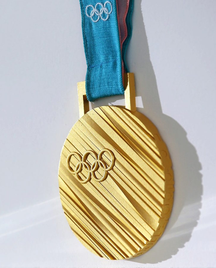 Gold+medal+from+the+2018+Winter+Olympics+in+Pyeongchang.+Labeled+for+reuse+under+Wikimedia+Commons.