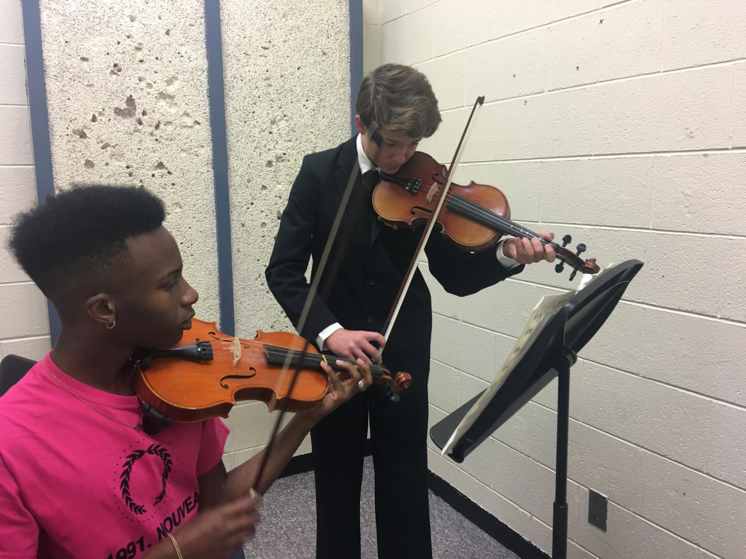 Senior Jordan Hubbard (left) and freshman Logan Fairhurst (right) practicing their Solo and Ensemble music piece.