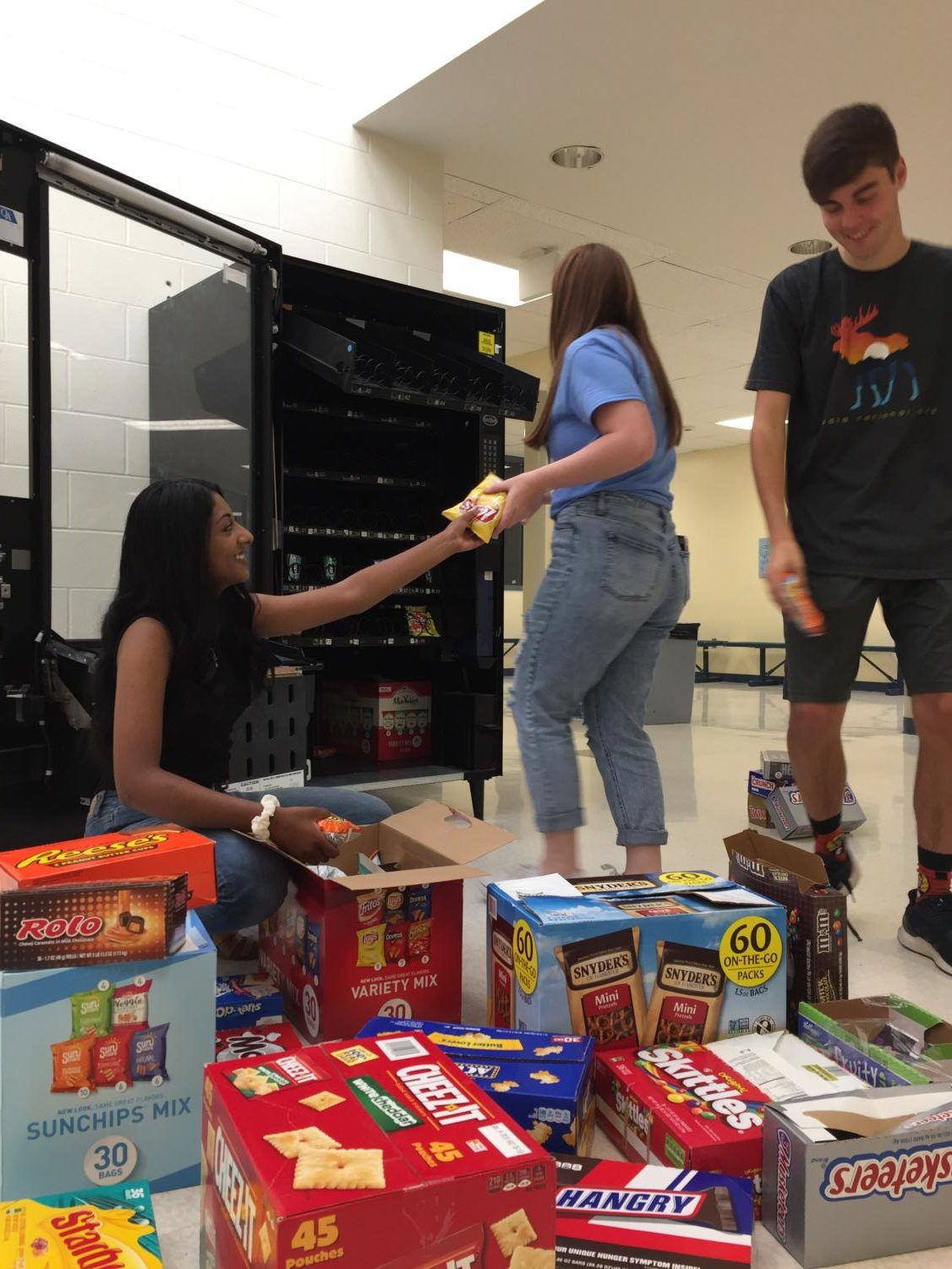 Air Academy's forensics speech and debate captains restock Lola during first period. Pictured left to right: Nidhi Unnikrishnan, Mackenzie Hardage, Sam Brooks.