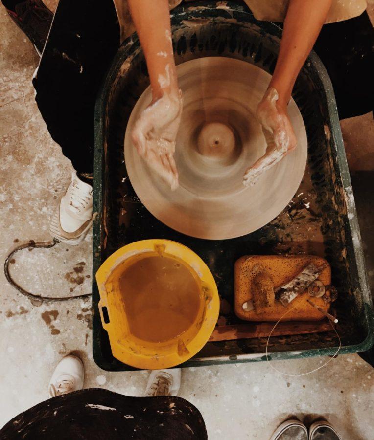 Connor Britton, a freshman at Air Academy, explores wheel throwing in ceramics class.