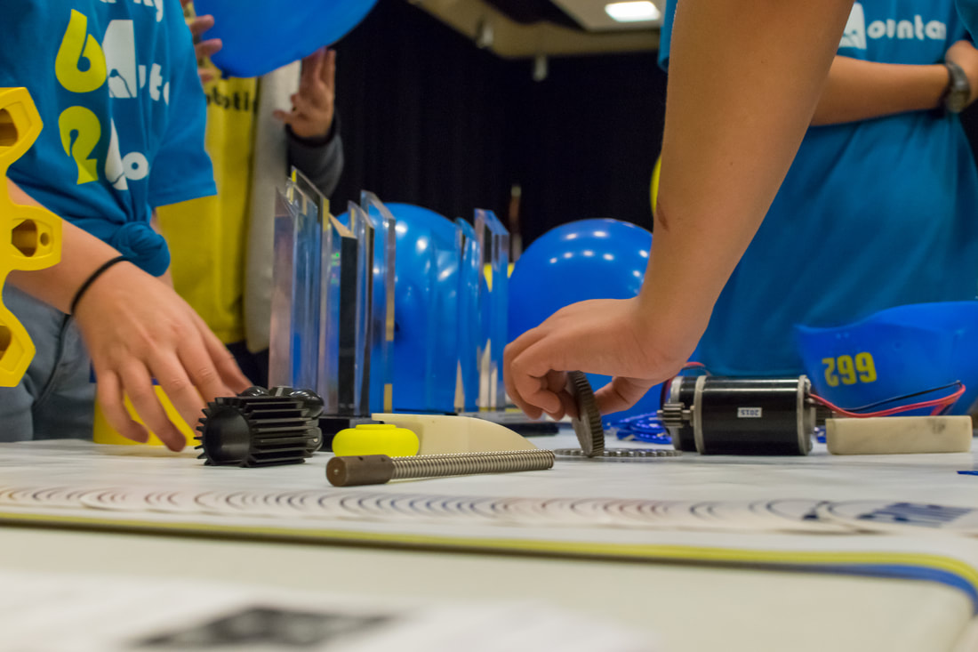 Students work on the robot with some of Team 622's many awards in the background.-Picture taken by student Grace Muncey