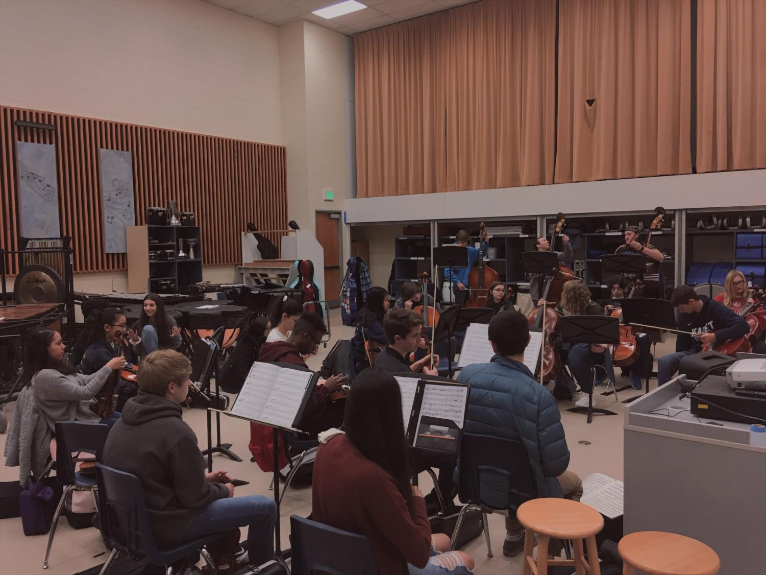 Orchestra warms up their instruments and prepares for instruction.