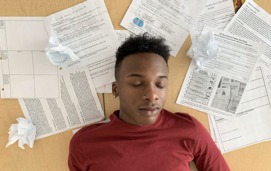 Senior Jordan Hubbard faints on a table amidst the mounds of homework he has accumulated from his 8 classes whilst struggling to maintain his 4.0 GPA.