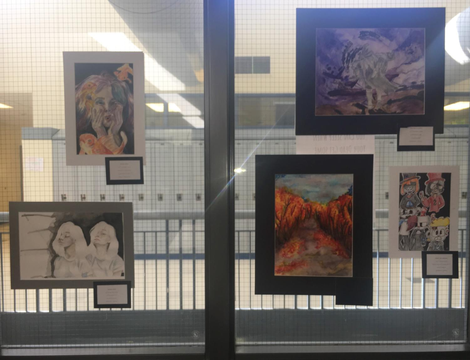 Art featured in the Air Academy Art Show with art from senior Emma Bryer on the left and junior Peyton Wyman on the upper right.