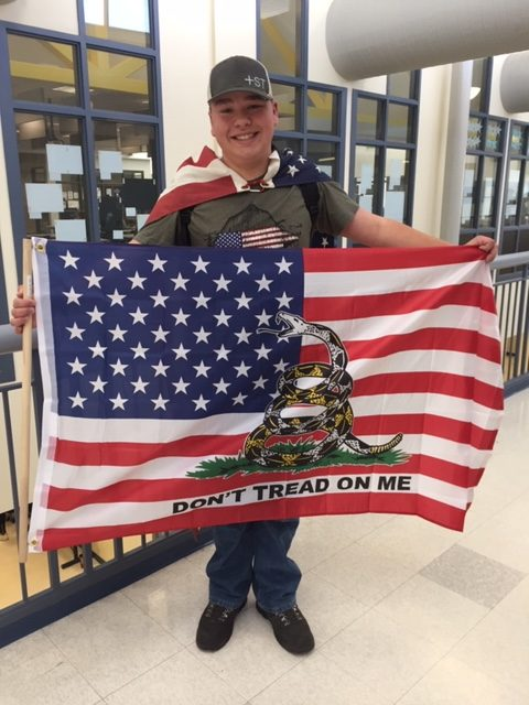 Freshman Rylan Baxter poses with American Gadsden Flag for red, white, and blue day during spirit week.