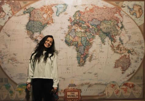 Junior Audrey Sandell posing with a smile in front of a world map at Kairos Coffee House.