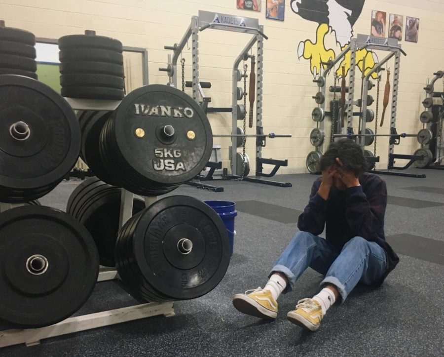 Junior Connor Dalrymple poses in the weight room to represent the disconnect between our perception of strength and emotional wellness.