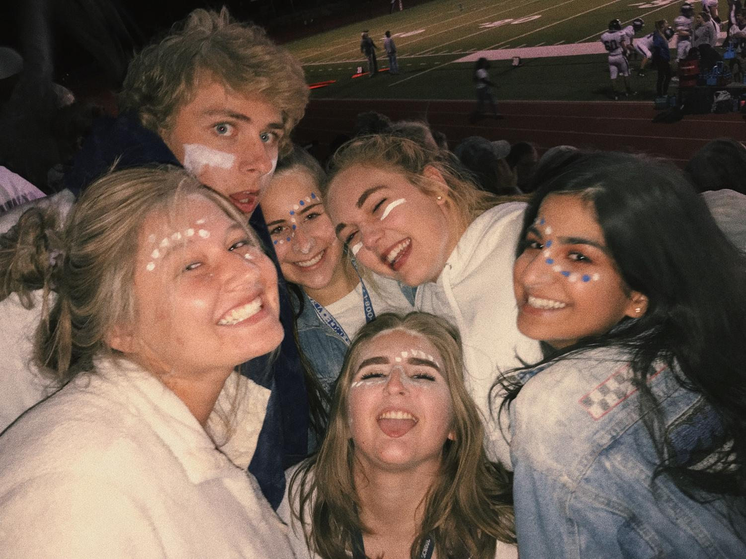 A group of AAHS juniors smiling at the white out football game at Cheyenne Mountain, captured moments after cups full of flour were thrown in the cold air. (Top row left to right: Carter Wood, Megan Pharris, Casey Hogan. Bottom row left to right: Acacia Ryska, Callissa Steel, Parmida Mahdavi.)