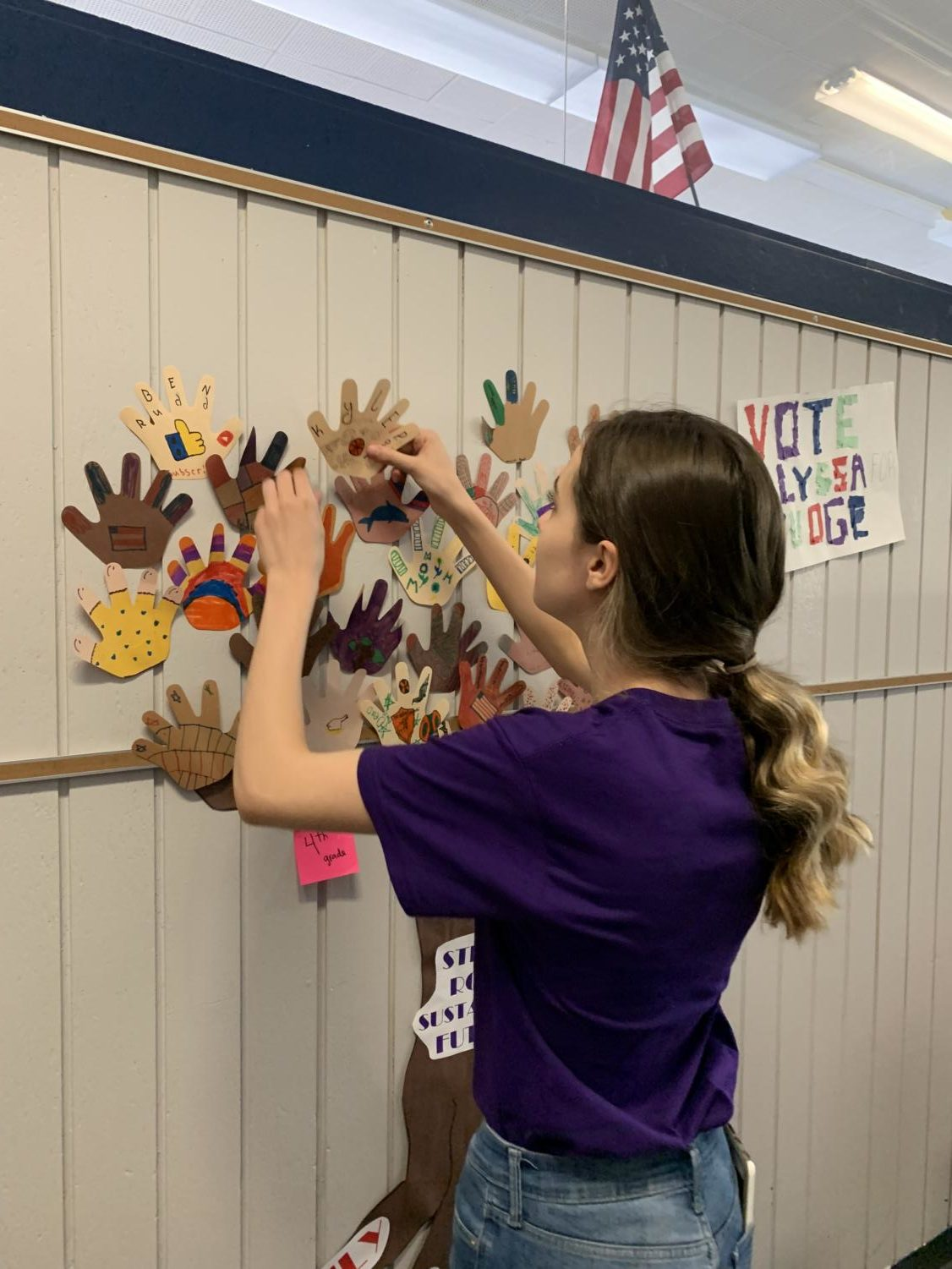 "Senior London Lenahan volunteers to help with crafts during ""Purple Up Day"" at Douglas Valley Elementary School, an event to celebrate military children"