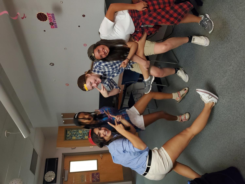 Junior Nathalia Eid, senior Beza Tefera, senior Rose Jones, and junior Alora Villarrael pose for frat boy day during Hoco spirit week.