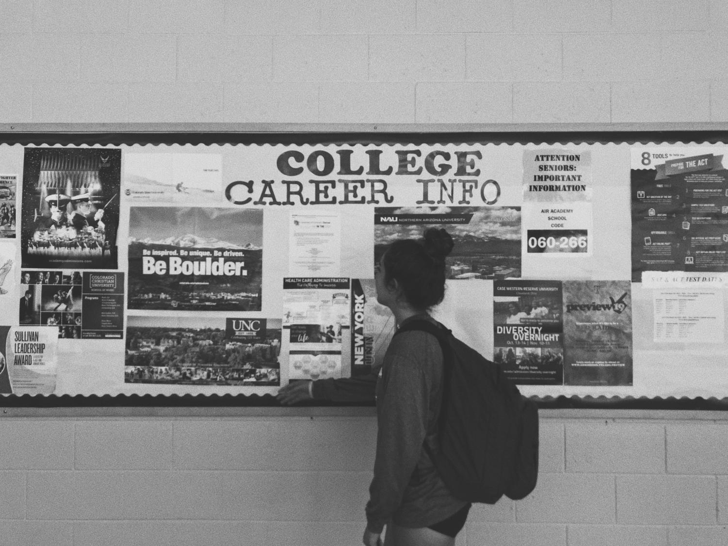 AAHS senior Nicole Lindsey standing in front of the student and services college wall, pondering the future decisions of college.