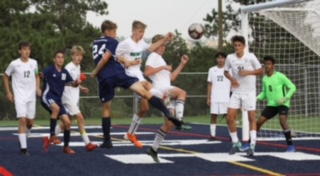 Rider Grow (24) challenging for a ball in the JV soccer game versus Niwot. Picture taken by Greg Slavens.