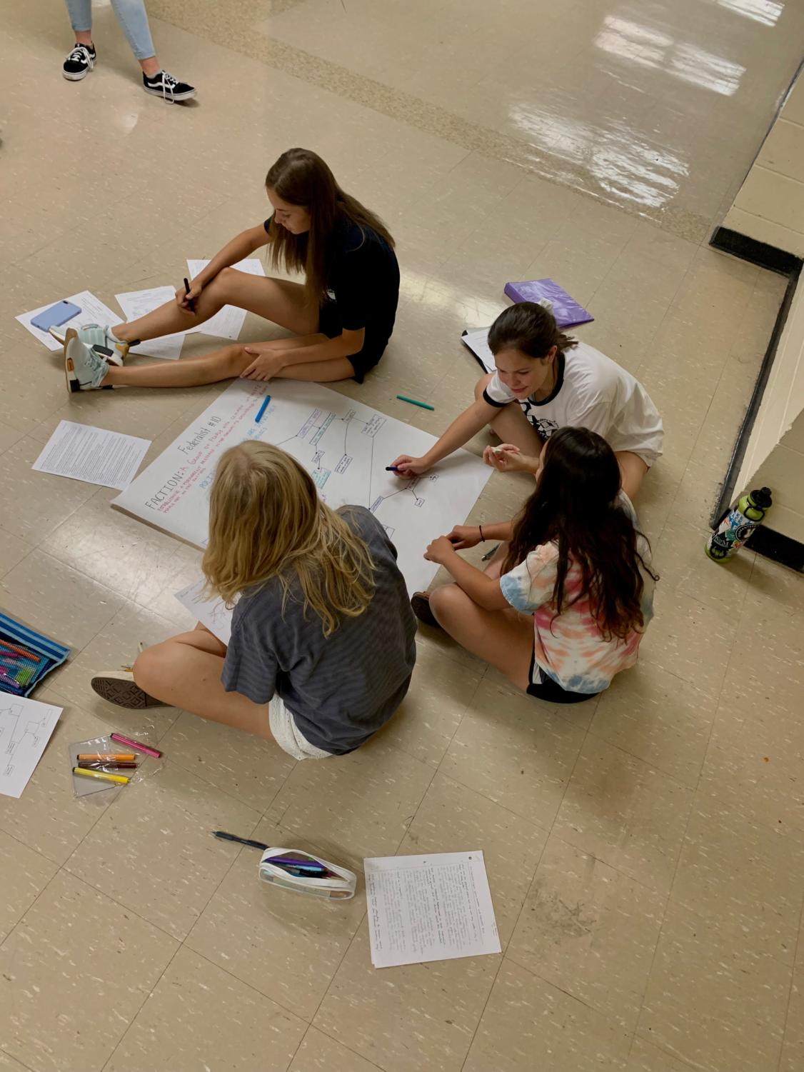 Seniors Gabi Robinson, Molly Matheson, Mary Waterman, and Brandy Beisinger all sit in the hallway and work on a project for one of their AP classes.