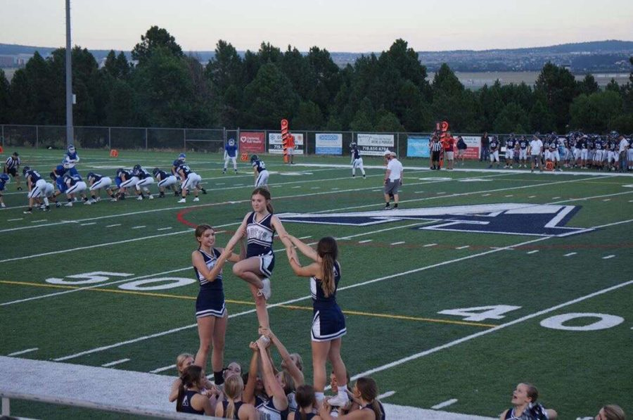 The+varsity+cheerleading+team+performs+a+pyramid+at+the+Blue+and+Silver+Game+on+August+23rd%2C+2019.