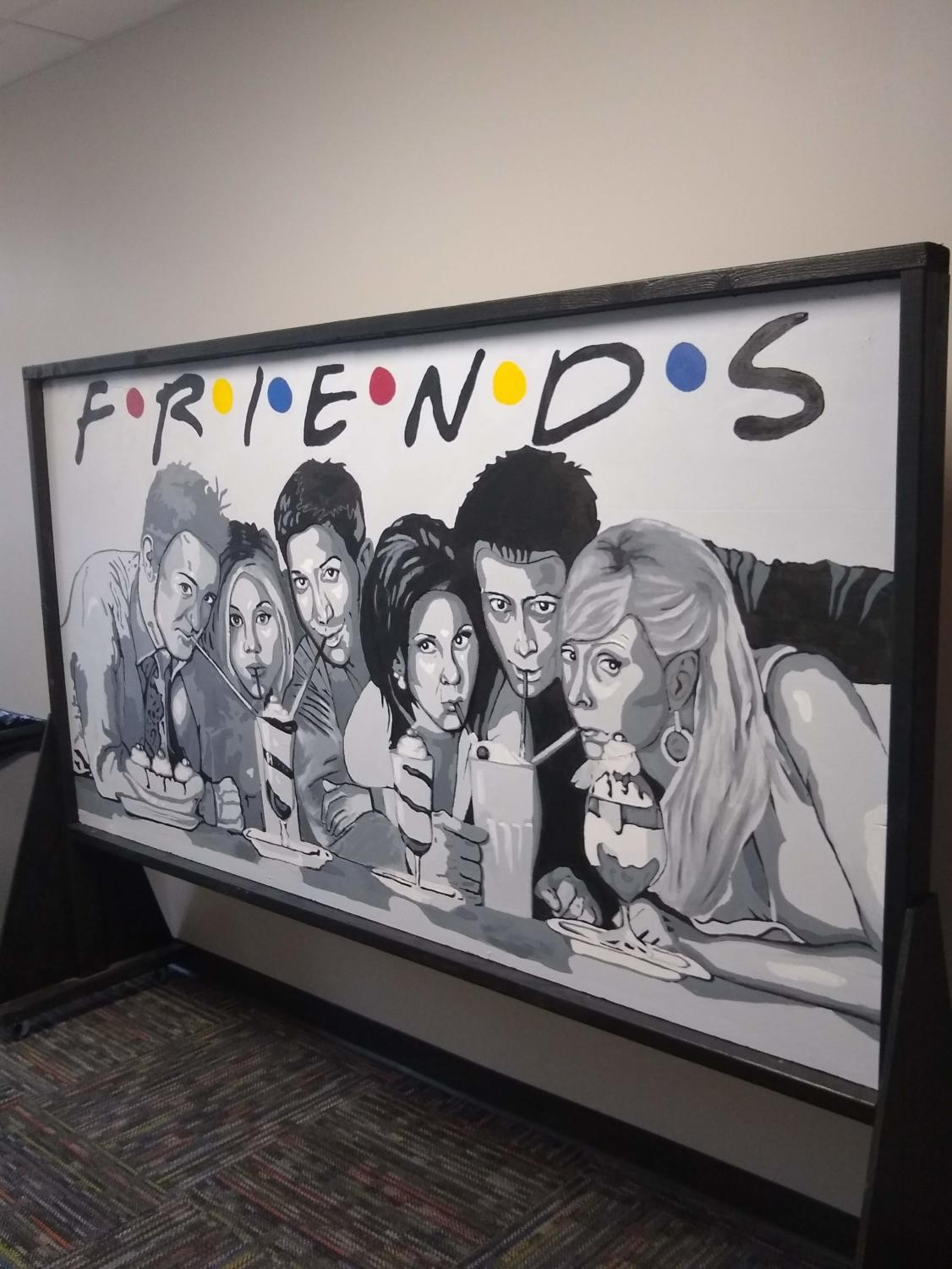 The Friends cutout poster, now filled in with faces, greets all who come into the library.