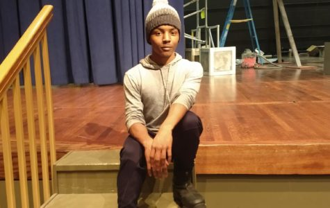Naheim Colon-Sanders sits onstage where many performances have been and where he hopes more will take place.