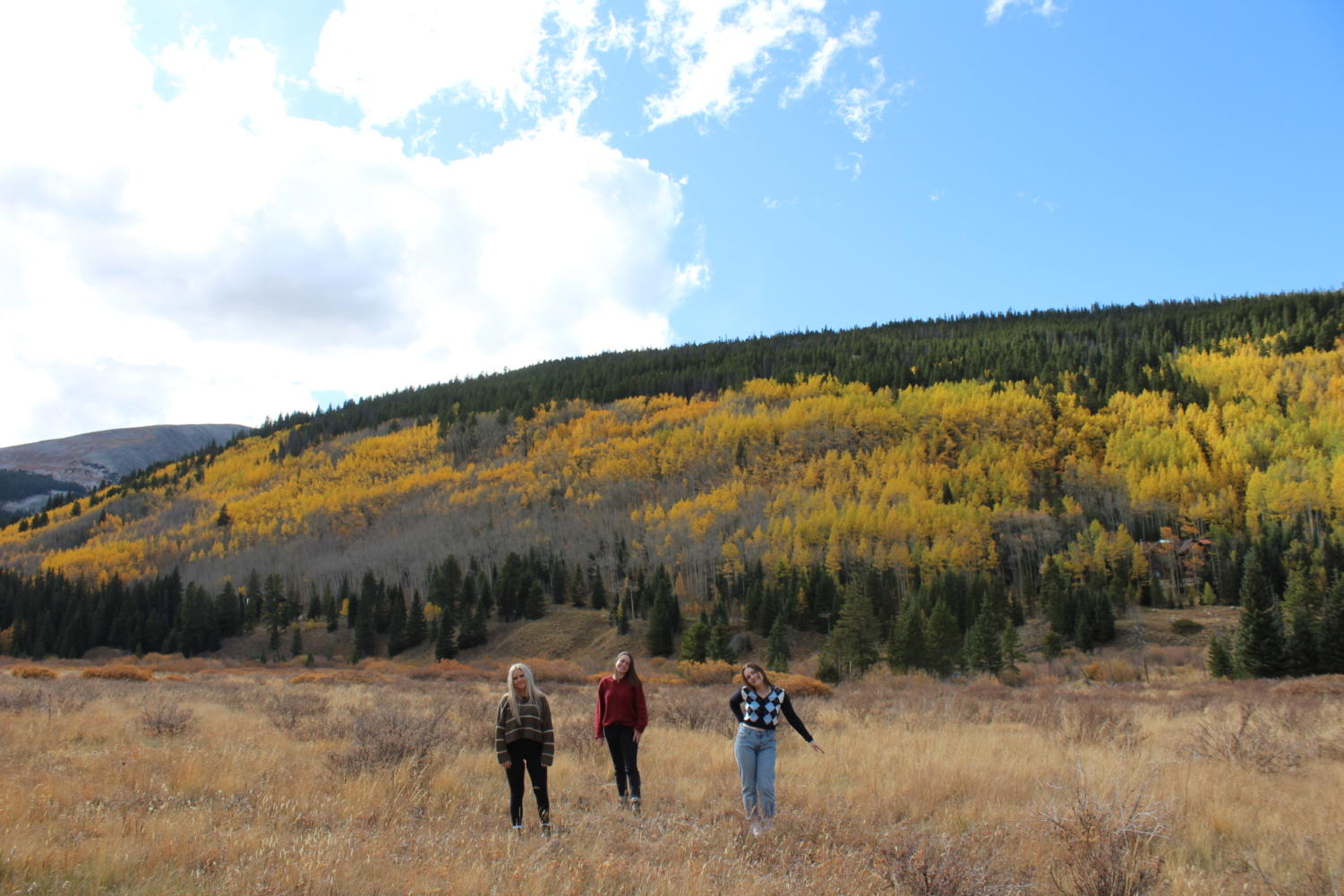 Seniors Sydney Pruitt, Megan Lockhart, and Campbell Fair pose in front of fall leaves in Breckenridge, Colorado.