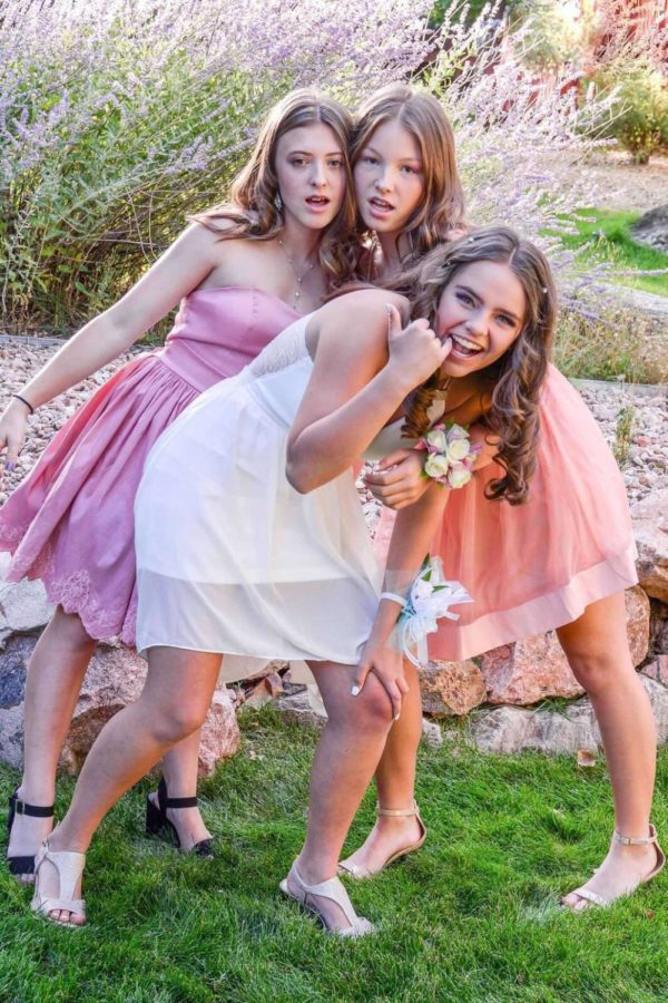 Freshmen Kiya Downs, Emme Van Beek and Ashlynn Olson take pictures before their first homecoming dance.