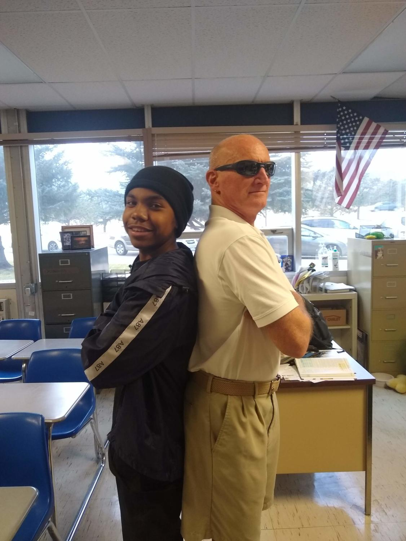 Junior Samuel Smith and math teacher David Calvano pose back-to-back, symbolizing the Boomer v. Gen Z conflict.
