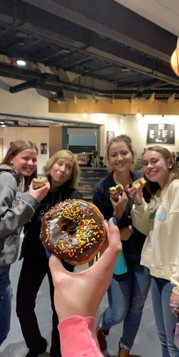 Senior Maddie Ross, Air Academy Juniors Emily Gregerson and Abby Cole and Abby's mom Shelley Cole all enjoy some delicious donuts after a small group event to kick off the holiday season.