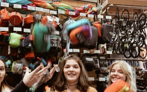 Seniors Emily Gregerson, Gabrielle Robinson, and Ruth Evilsizer toss hammocks inside an REI Co-op, feeling excited to hang their new hammock up.
