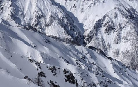 A snow-filled mountain range shows the potential for fun but also danger due to avalanche risks.