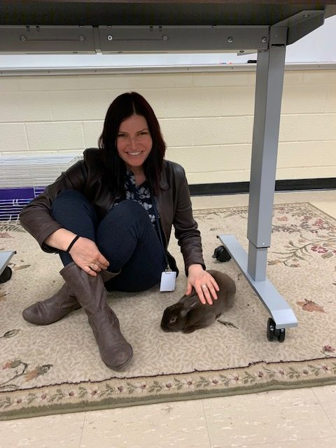 Ms. Valladares pets her rabbit, Fernando, in room 417.