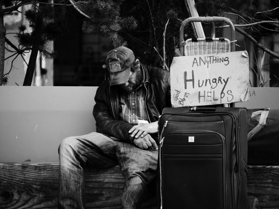 A+homeless+man+carries+a+sign+depicting%2C+%22Anything+Helps%22+in+hope+of+drawing+the+generosity+of+a+passerby.+Photo+labeled+for+reuse+by+Steve+Knutson+on+Unsplash.com