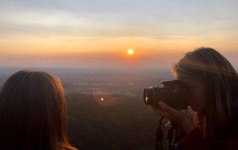 Senior Elina Landin takes a photo of senior Tatum Miller with lighting from a sunrise.