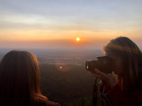 Senior Elina Landin takes a photo of senior Tatum Miller with lighting from a sunrise.