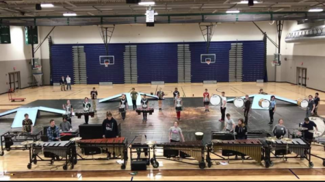 The full Academy Winter Percussion ensemble stands in position before beginning a practice run.