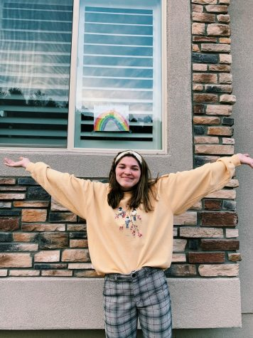 Senior Ruth Evilsizer stands outside in front of a rainbow with arms wide open for everything in store after quarantine.