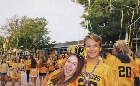 Seniors Megan Lockhart and William MacGuire smile in front of the senior sunrise chaos.