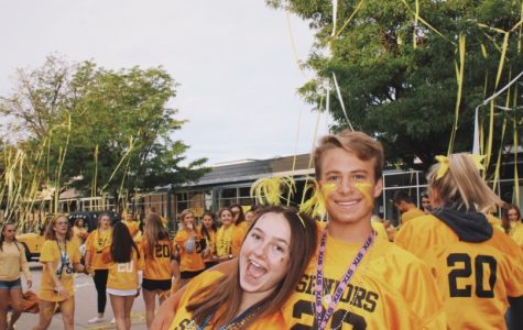 Seniors Megan Lockhart and William MacGuire smile in front of the senior sunrise chaos.