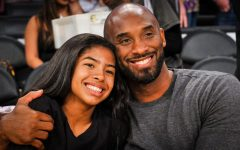 Image labeled for reuse by Insider.com. Kobe Bryant and Gigi Bryant watch a Lakers game together.