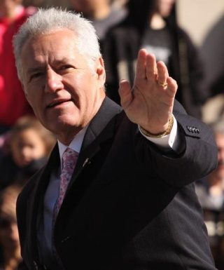 Alex Trebek waves to the crowd at a 2009 event. Labeled for reuse by Wikimedia Commons.
