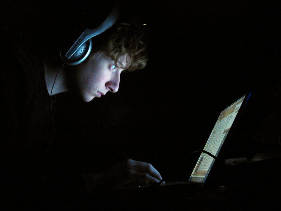 Labeled for Reuse under the Creative Commons. A man stares at a computer screen while being surrounded in complete darkness.