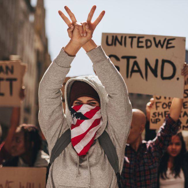 Woman with mouth covered gesturing peace sign with both hands on road. Group of women protesting silently on road.