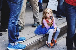 Labeled for Reuse by Creative Commons. A young girl wearing a superhero costume eats ice cream on the sidewalk while watching a crowd pass by.