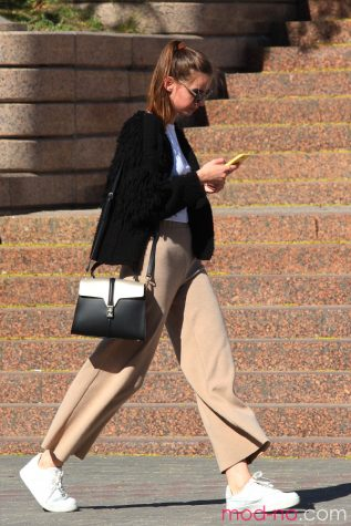 A woman goes about her day wearing a button up with dress pants and a black jacket. Labeled for Creative Commons.