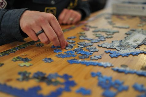 An individual attempts to solve this dark blue jigsaw puzzle. Labeled for Reuse by Creative Commons.