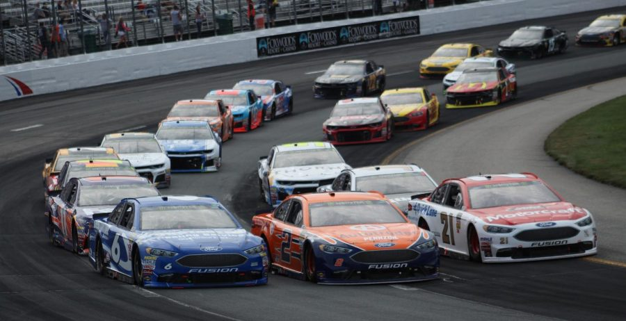 NASCAR drivers race hard in a 2018 race at New Hampshire Motor Speedway. Labeled for reuse by Wikimedia Commons.