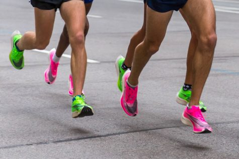 """""""Legs of marathon runners wearing Nike ZoomX Vaporfly Next% running shoes in the pink and green versions"""" Marco Verch flickr creative commons."""