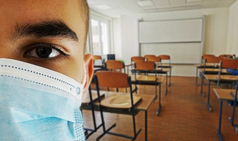 A man wears a mask in the classroom. Labeled for reuse by pixabay.