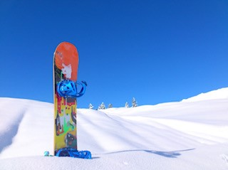 Labeled for Reuse by Creative Commons.  A colorful snowboard embedded into a white patch of snow standing vertically while a nice day is out. Snowboarding and skiing are possibly the most renowned winter sports today. And they often draw large crowds to their resorts from all over the world.