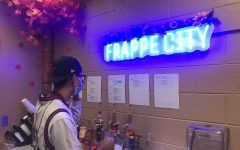 Kadet Coffee Employee Tatum Norris posing as he looks at a recipe for a Vanilla Bean Frappe.